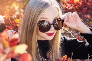 Autumn woman in colorful red leaves