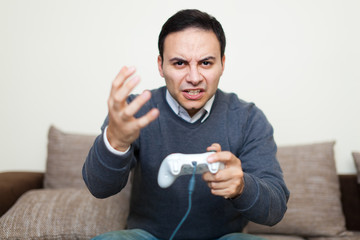 Angry man playing videogames on his sofa