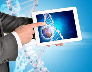Man hands using tablet pc. Image of Earth and DNA helix on