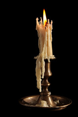 Burning Candle In Old Silver Candlestick Isolated on a Black