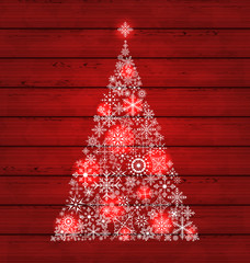 Christmas fir made of snowflakes on wooden background