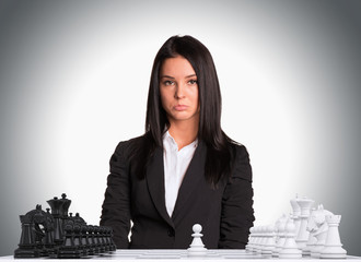 Upset businesswoman looking at camera. Chessboard with chess