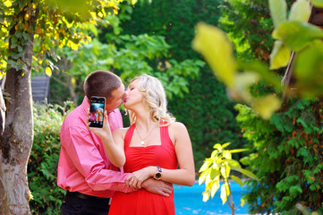 happy man and woman kiss and make self on phone