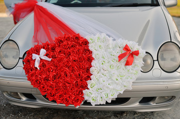 Wedding car decorated with two hearts made of flowers