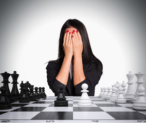 Businesswoman covering her face with hands. Chessboard and chess