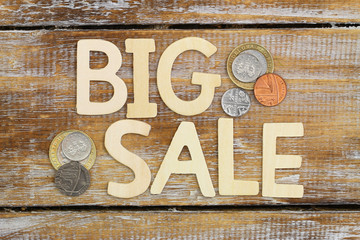 Big sale written with wooden  letters on rustic surface