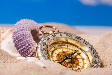 Sea shells  and compass on  sand and blue sky Background