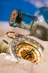 Sea  shells  and compass on  sand and blue sky