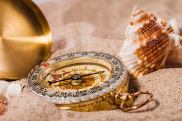 Sea  shells and  compass   on  sand