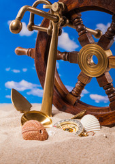 Sea  shells   compass  and brass anchor on  sand