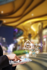 Businesswoman sending email in front of the shopping mall