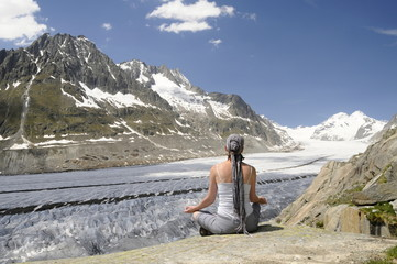 girl in yoga position above the glacier