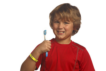 Happy boy in red holding up toothbrush