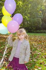 girl holding balloons