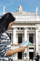 Young woman studying map near the burgtheater