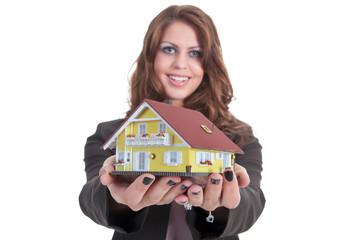 Junge Bank Frau überreicht symbolisch Miniatur Haus
