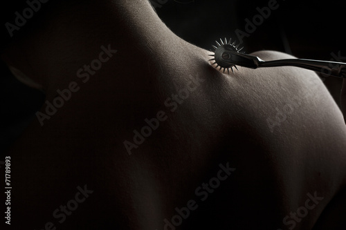 Foto op Aluminium Akt Nude submissive woman shoulder, bdsm act with Wartenberg wheel
