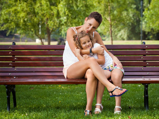 Mother embracing  her little daughter while sitting