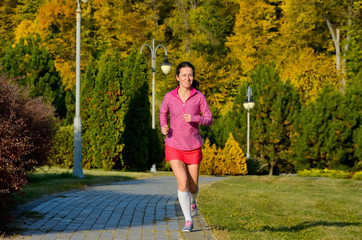 Woman running in autumn park, girl runner jogging outdoors
