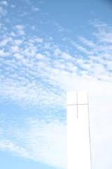 Weißer Kirchturm vor weiß-blauem Himmel