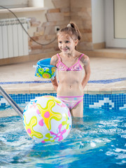 little girl playing with beach ball at indoor swimming pool