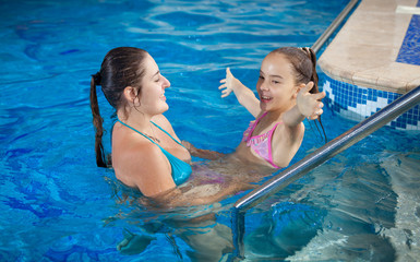 beautiful mother playing with daughter at swimming pool