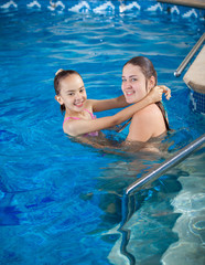 mother holding daughter on water surface and teaching how to swi