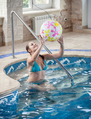 beautiful young woman playing with beach ball at swimming pool