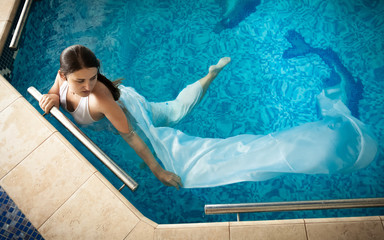 woman in white dress swimming next to edge in swimming pool