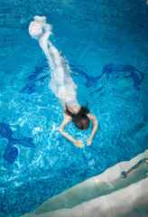 woman in long white dress diving underwater at swimming pool