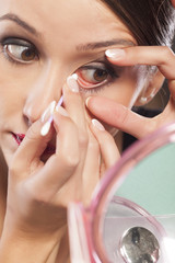 young beautiful woman clean her eye with hygienic swab