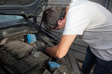 homme en train de réparer sa voiture
