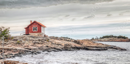 Leinwanddruck Bild Red house at sea shore in dull colors at autumn