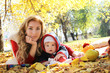 Mother and baby girl playing in autumn park