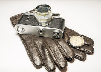 Film camera, pocket watch and leather gloves