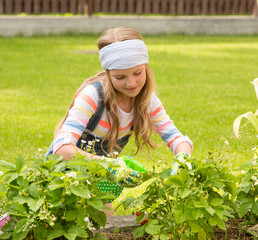 girl cares for the plants in the garden