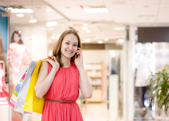 Happy young woman with bags talking on the phone