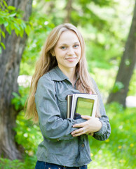 portrait of beautiful girl holding books in their hands
