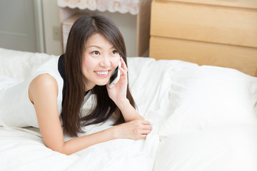 ベッドで電話をする女性