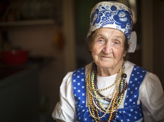 Portrait of Slavic grandmother in traditional clothes indoors.