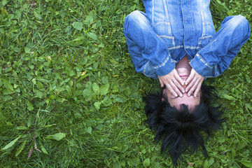 Girl in a denim jacket lying on the grass