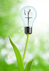 Bulb with wind turbine on plant - green energy concept