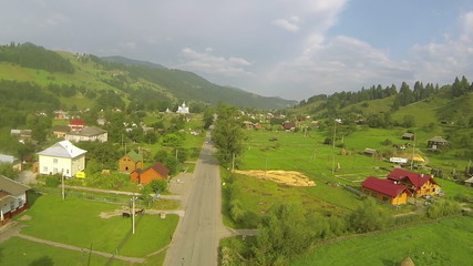 road in  mountain valley with village. Aerial  shot