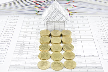 Row of gold coins in front of house
