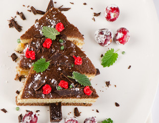 Tree made of  cake with christmas decorations on  white plate