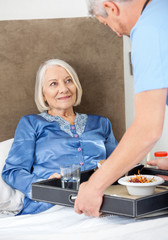 Caretaker Serving Breakfast To Happy Senior Woman