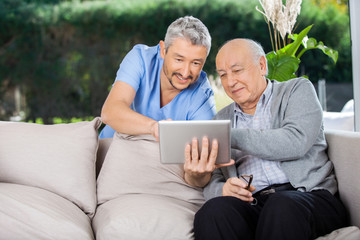 Male Caretaker And Senior Man Using Tablet PC
