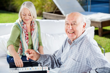 Happy Senior Man Playing Rummy With Woman