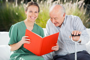 Portrait Of Happy Female Nurse Reading Book For Senior Man