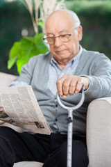 Elderly Man Reading Newspaper At Nursing Home Porch